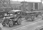 View of the travelling crane loading one of the GWR's mechanised tractor and trailer at Queens Head yard in the early 1930s