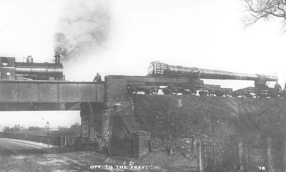 View of the short train carrying the 15 inch gun barrel which is sandwiched between two 0-4-0ST locomotives as it passes over an unknown road