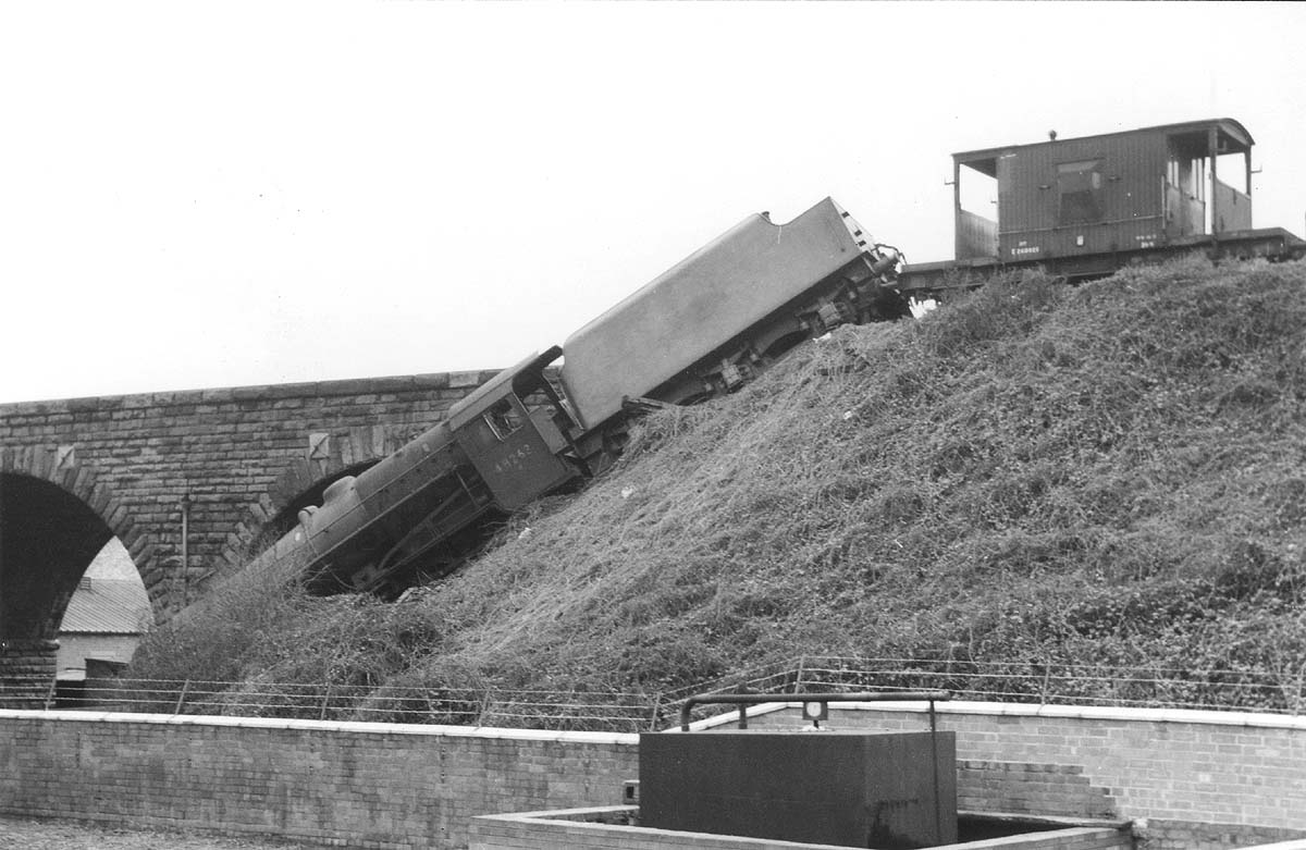 Ex-LMS 8F 2-8-0 No 48263 is seen lying down the embankment after running through the buffers on 16th December 1962