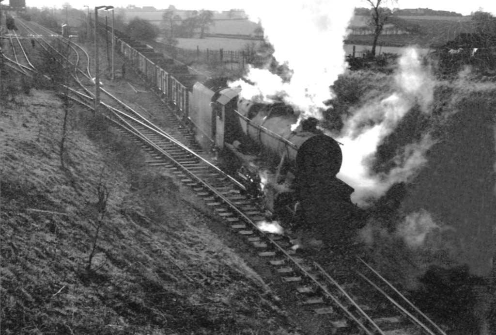 An unidentified ex-LMS 2-8-0 8F is seen at the head of an empty wagon train bound for Kingsbury Colliery