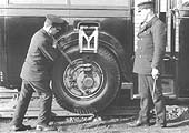The driver uses a lever to raise the road wheel on the eccentric, the man on the right holds one of the holding pins